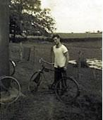 Sgt. O'Neil wearing a white t-shirt, stands next to a bicycle